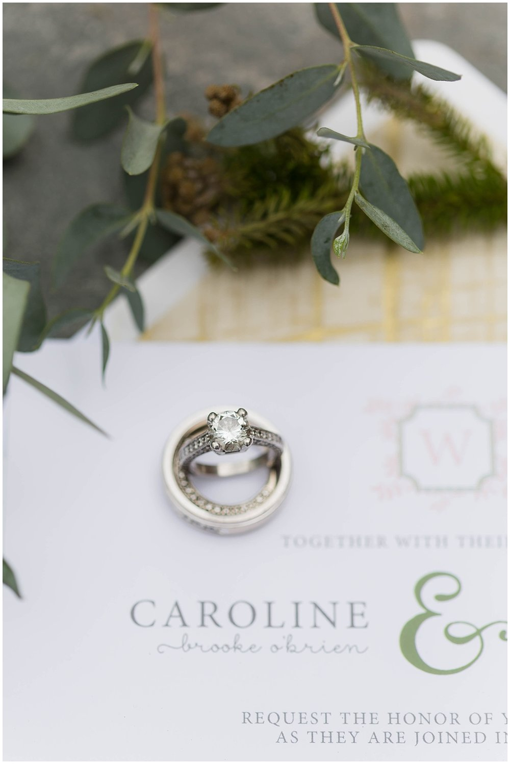 silver wedding rings on invitation suite