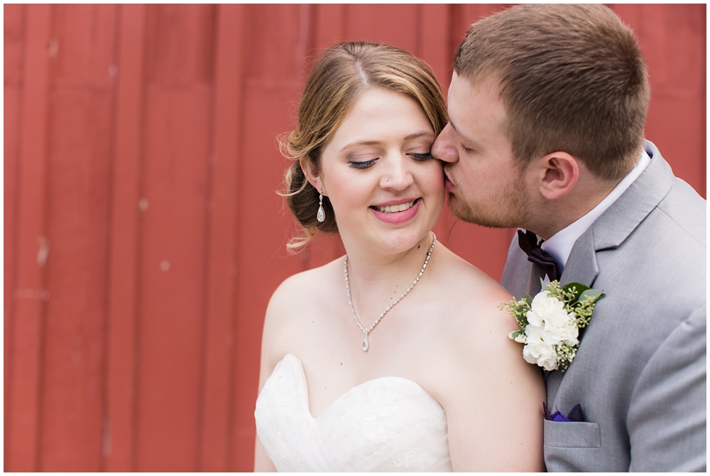 wedding portrait of bride and groom in front of red barn