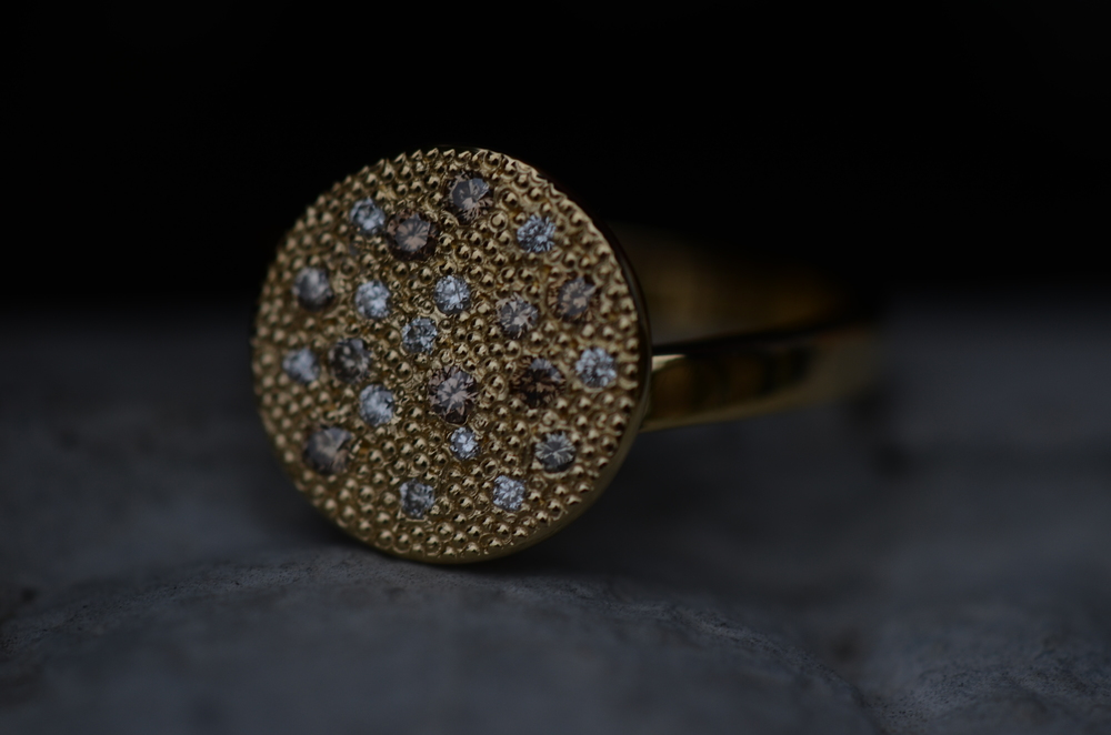 A hand-made 18KY gold textured disc-top ring, set with natural white, light brown, and cognac colored brown diamonds.