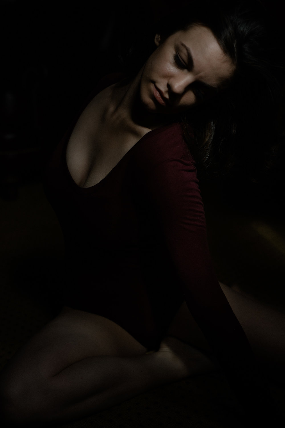 a portrait of emma grimsley in a victorian airbnb in dayton, ohio. photograph by sarah rose walk of sarah rose photography. emma is sitting on the ground, and she is looking to the side, twisting her body. emma is wearing a long sleeve burgundy red bodysuit.