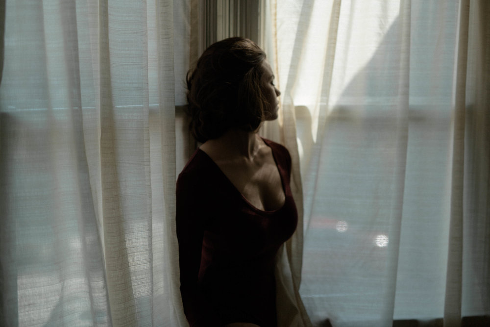 a portrait of emma grimsley in a victorian airbnb in dayton, ohio. photograph by sarah rose walk of sarah rose photography. emma is behind a cream colored sheer curtain and is gazing out the window behind her. emma is wearing a long sleeve burgundy red bodysuit.
