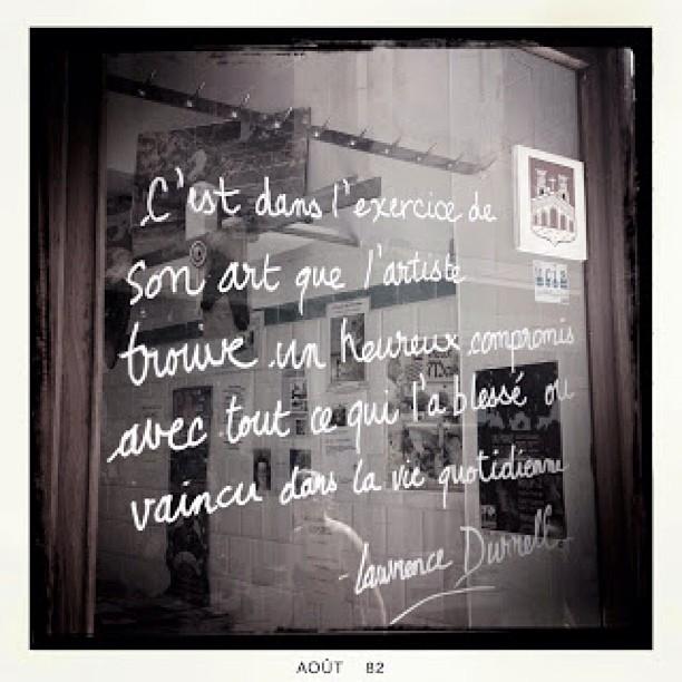 """Écriture figurant dans une vitrine au centre ville à Sommières, France.  """"C'est dans l'exercice de son art que l'artiste trouve un heureux compromis avec tout ce qui l'a blessé ou vaincu dans sa vie quotidienne.""""  Laurence Durrell"""