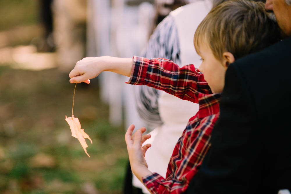 Young guests plays with leaf at outdoor Fall wedding