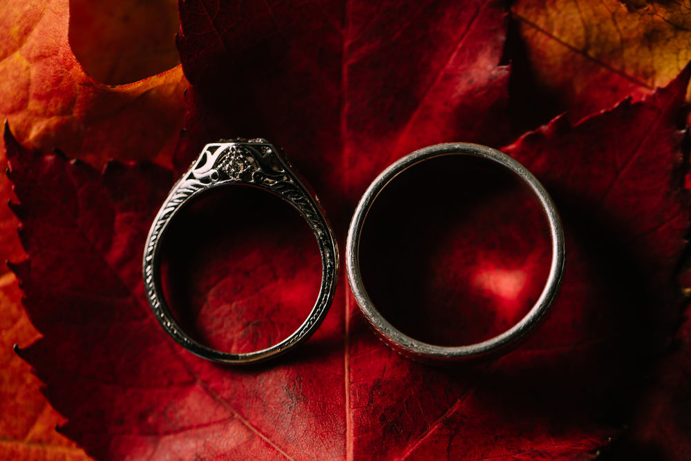 Bride and groom's rings photographed on a bright red fall leaf