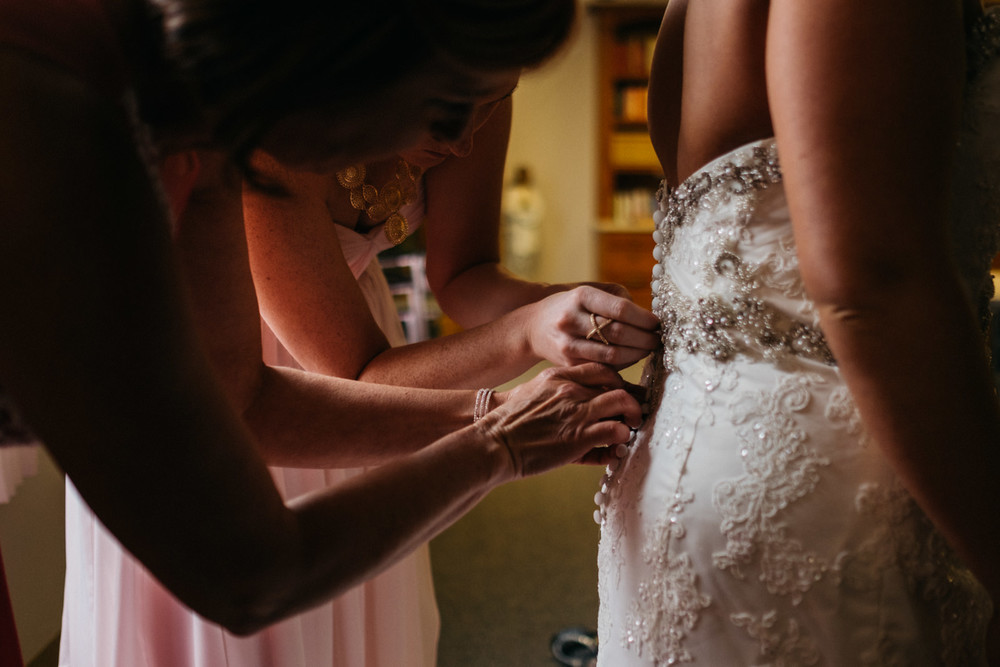 Bride getting in dress with help of bridesmaids