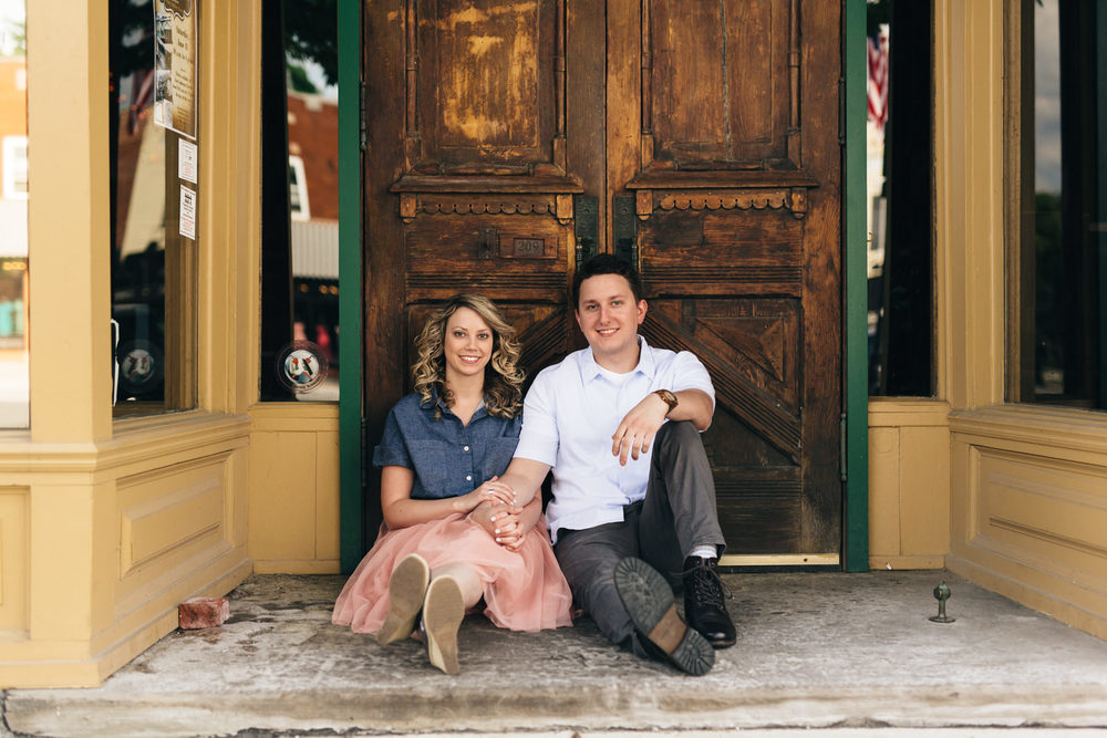 Couple sitting in front of historical wooden door in downtown Perrysburg, Ohio.