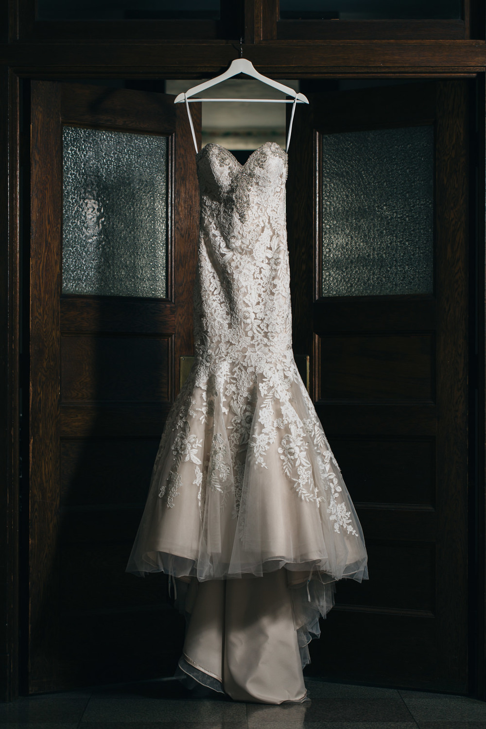 Beautiful vintage lace wedding dress hanging at Nazareth Hall.