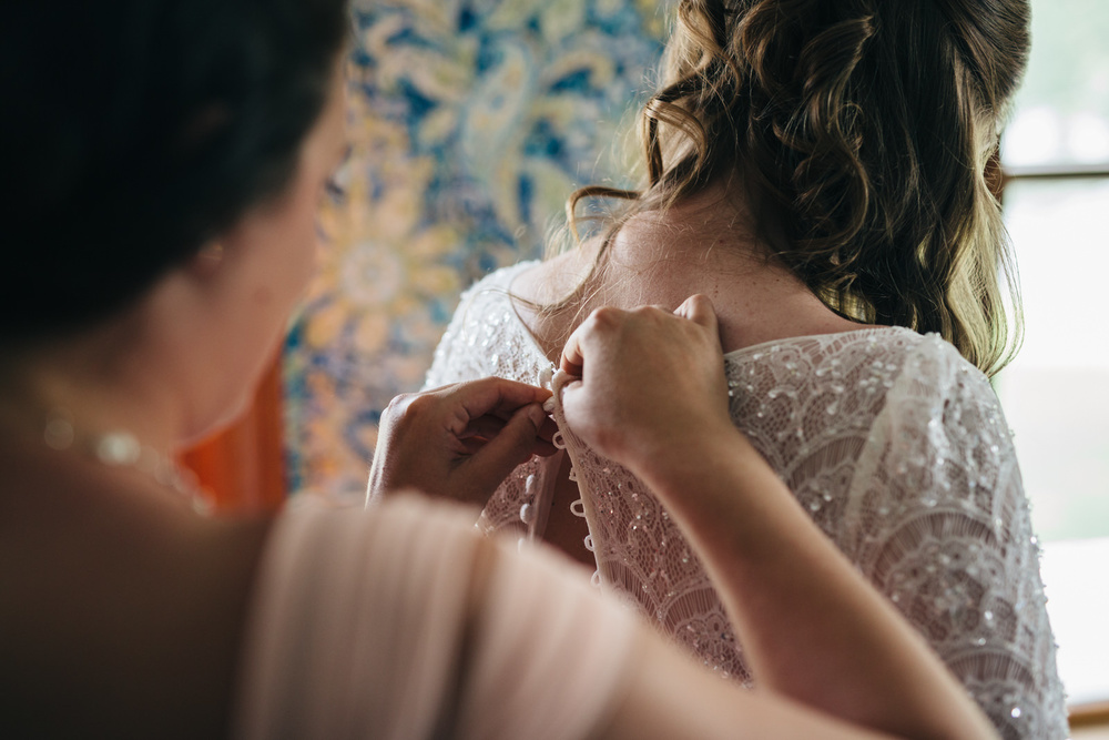Bride getting into her vintage lace wedding dress.