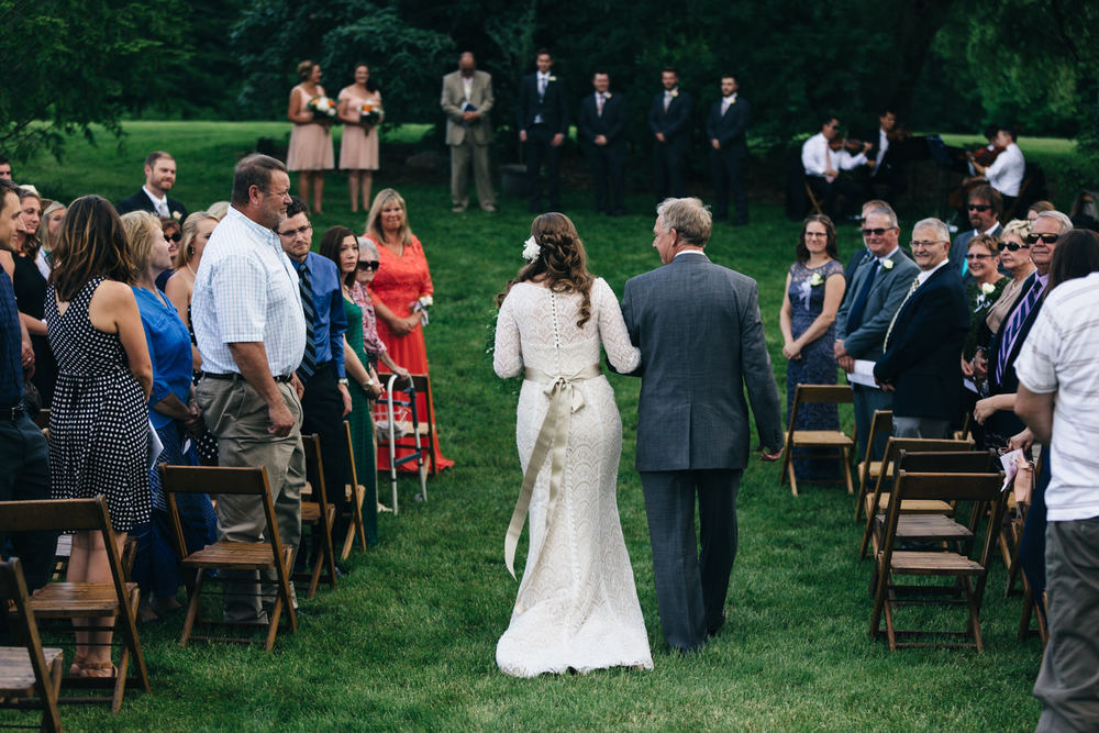 Bride walks down the aisle with her father during summer wedding at Quailcrest Farm.