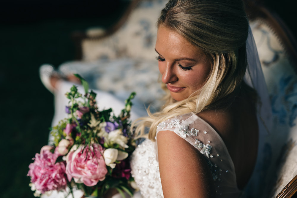 Bridal portrait with beautiful floral bouquet during summer wedding.