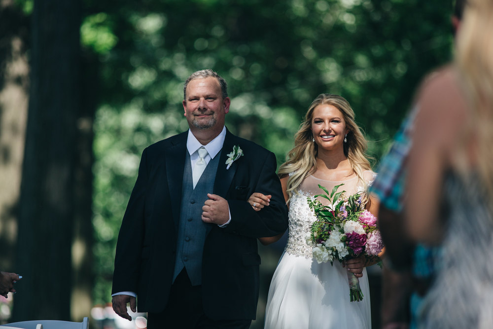 Bride walks down the aisle with her father during outdoor wedding ceremony at Oak Shade Grove.