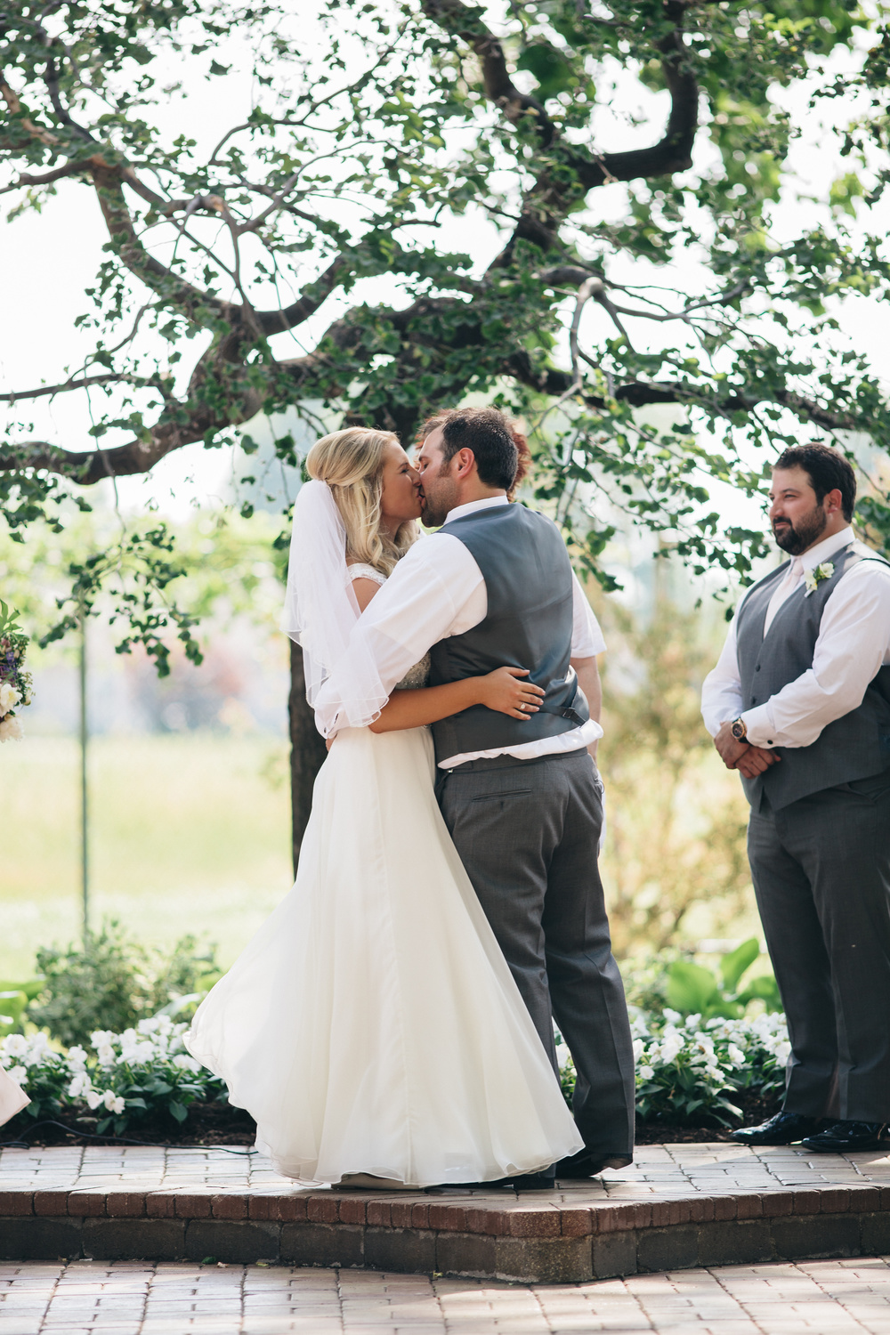 First kiss between bride and groom during outdoor ceremony.