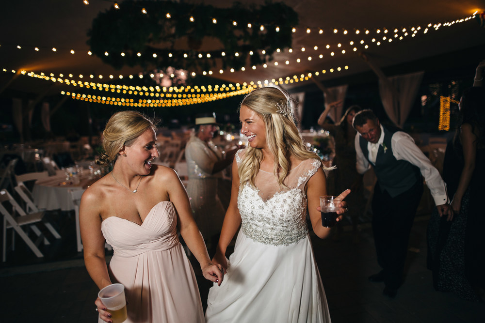 Bride dancing with bridesmaid at wedding reception in Toledo, Ohio.
