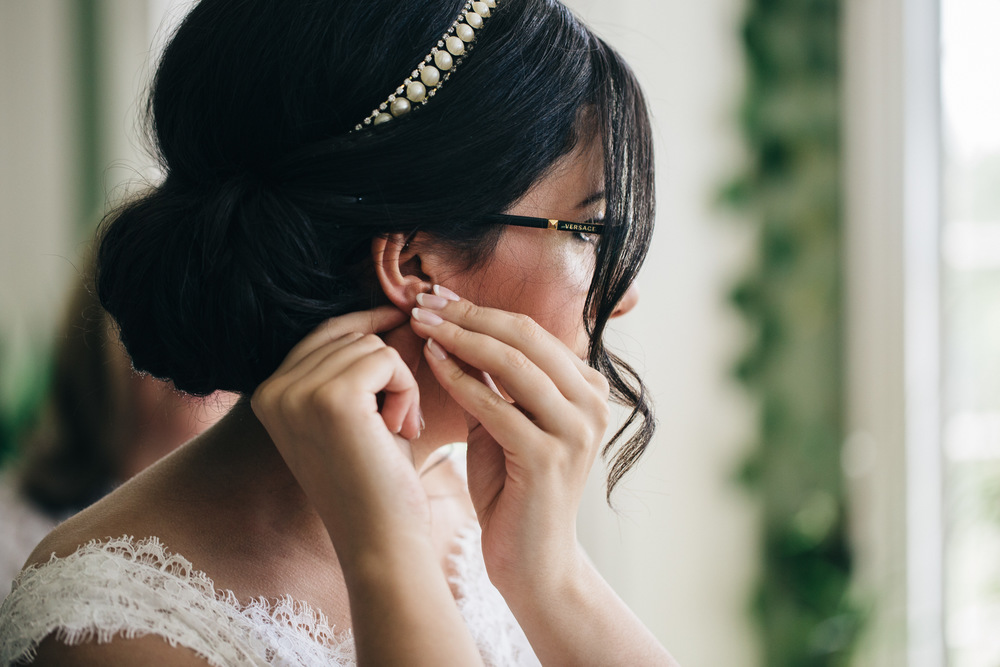 Bride in lace wedding dress puts earrings in on wedding day.