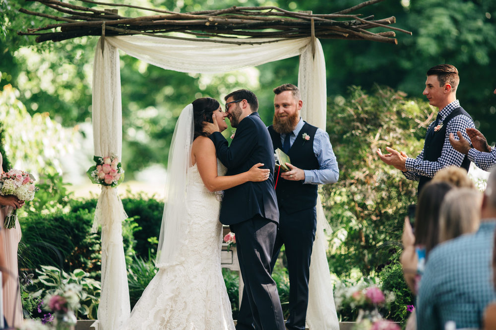 Bride and groom kiss at wedding ceremony in garden at Hoover Park