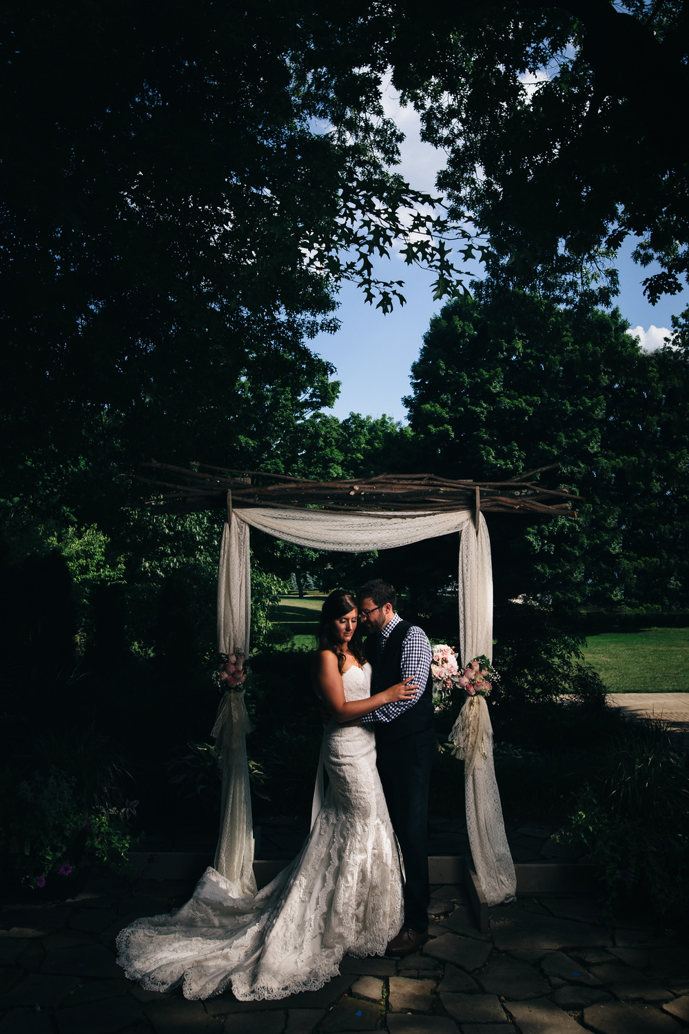 Bride in lace wedding dress with groom in navy blue suit after ceremony.