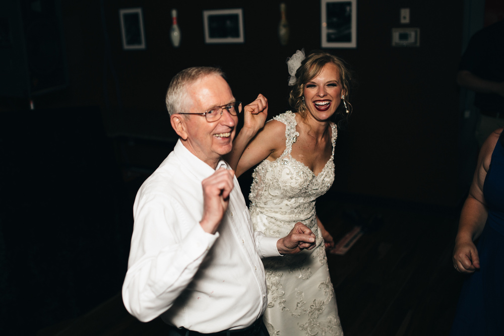 Bride dances with father in law during wedding reception.