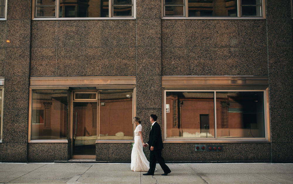 Bride and groom walking through downtown Toledo.