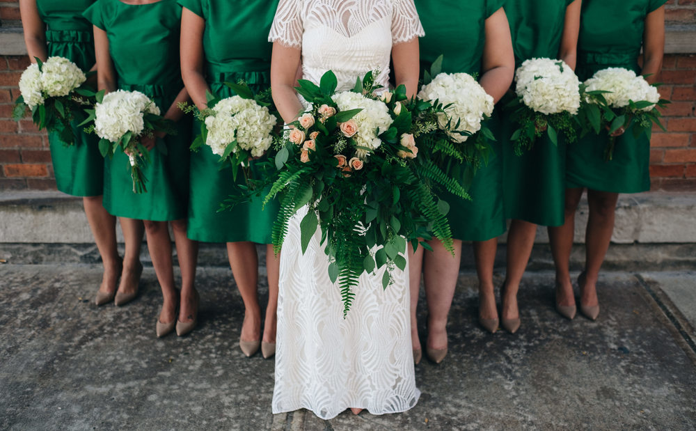Bridesmaids floral arrangements in emerald green wedding.