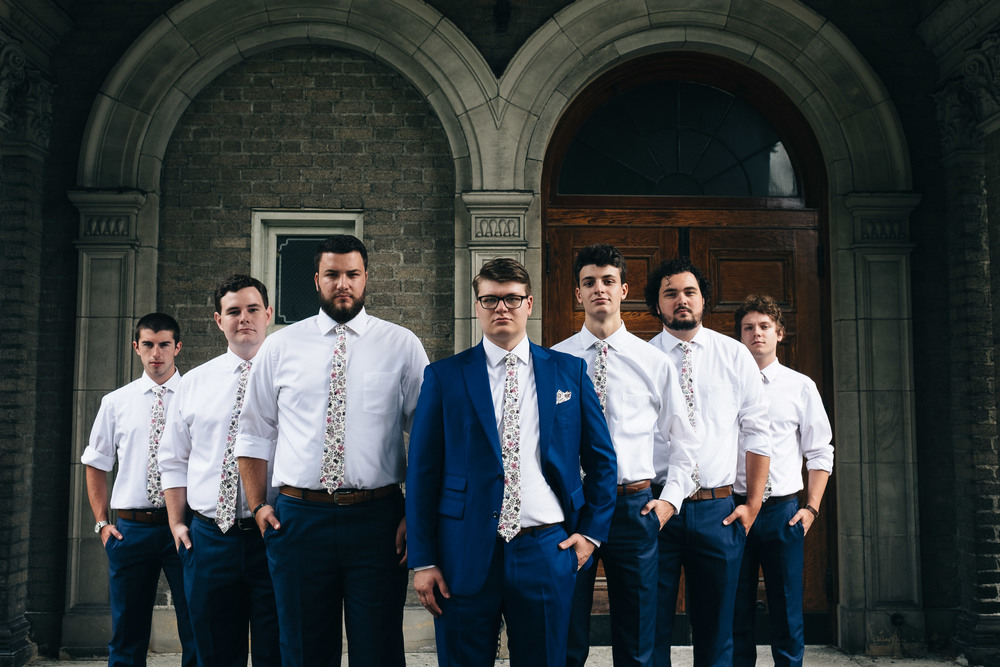 Groomsmen in floral ties and navy blue suits.