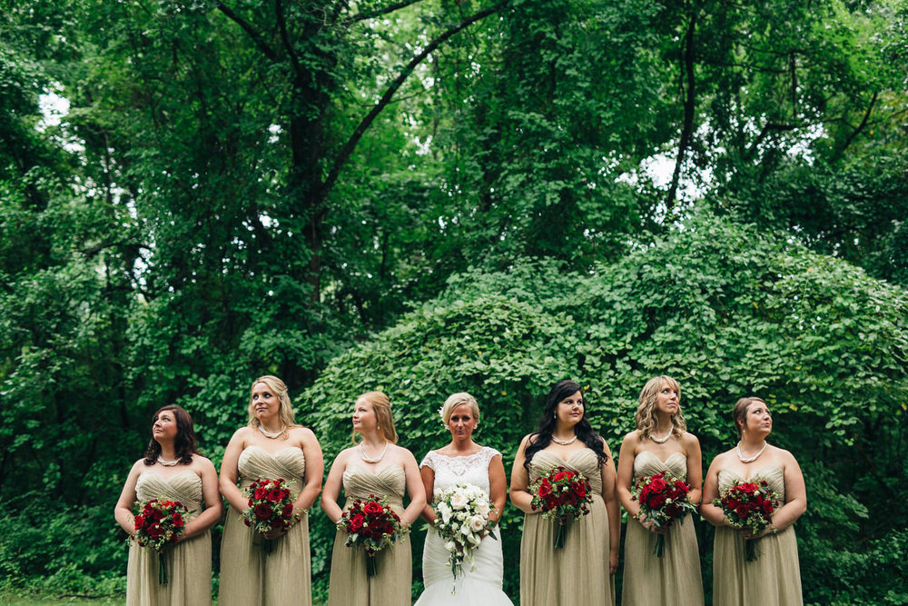 Bridesmaids in gold dresses with merlot floral bouquets.