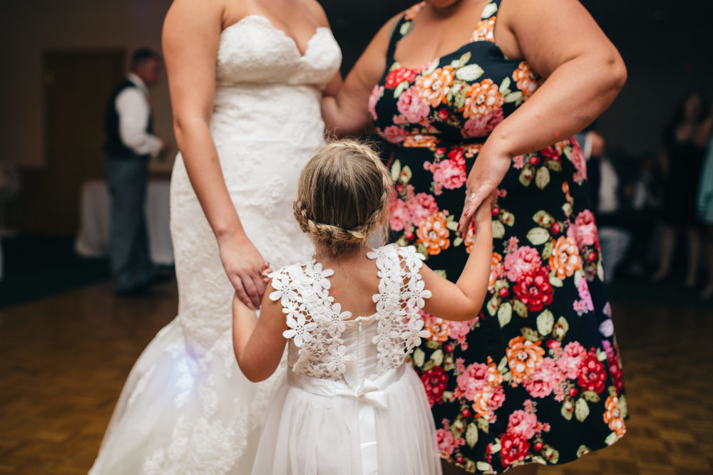 Flower girl dancing with bride at wedding reception