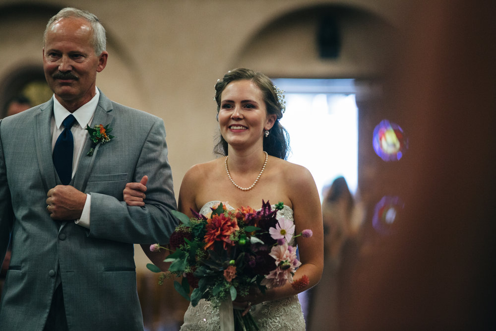 Bride walks down aisle with father at wedding ceremony.
