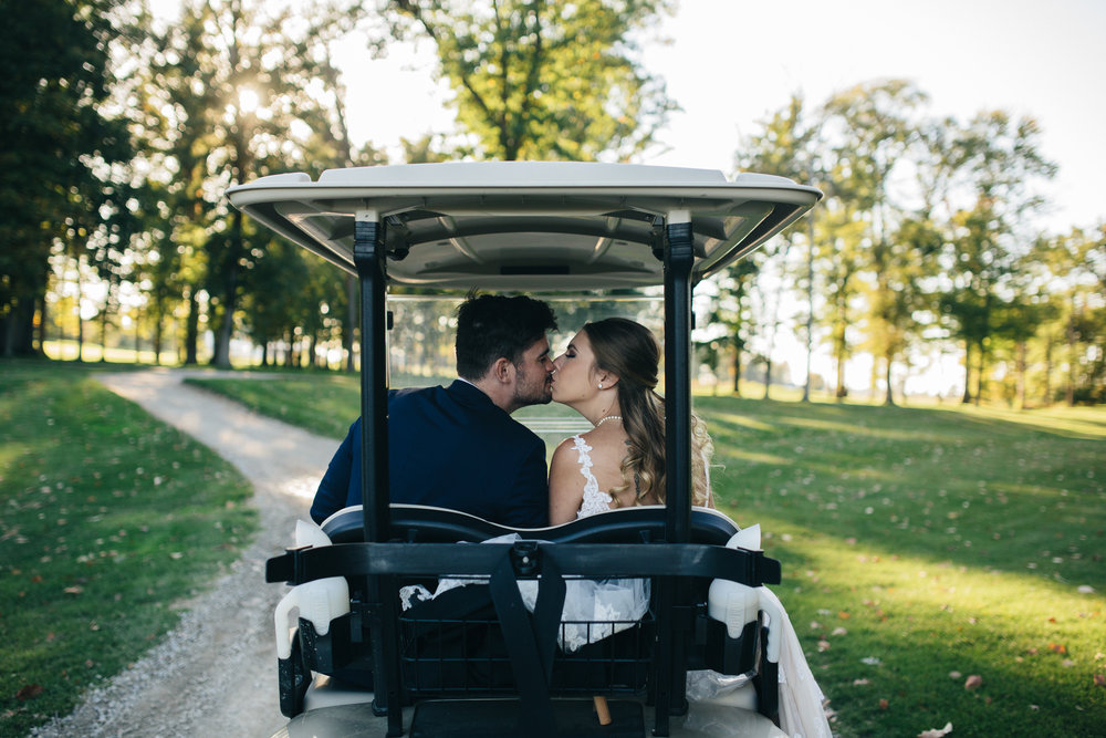Bride and groom ride away in golf cart at Stone Ridge Golf Club in Bowling Green, Ohio.