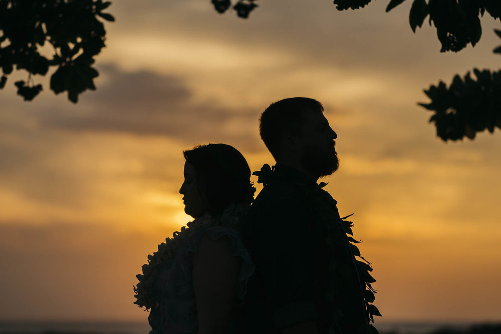 Bride and groom stand back-to-back during Hawaiian sunset in Kona, Hawaii.