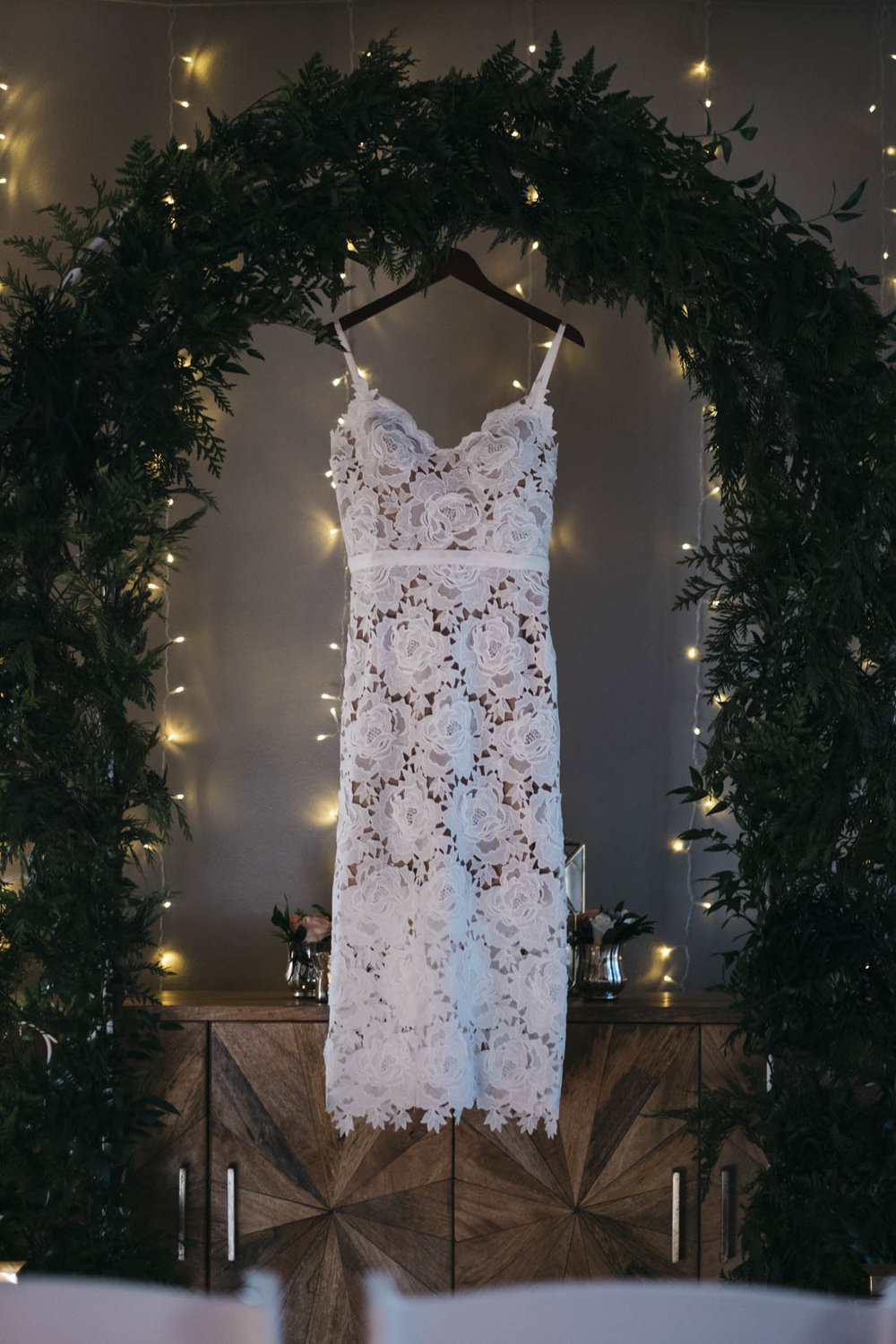 Wedding dress hanging in archway in home.