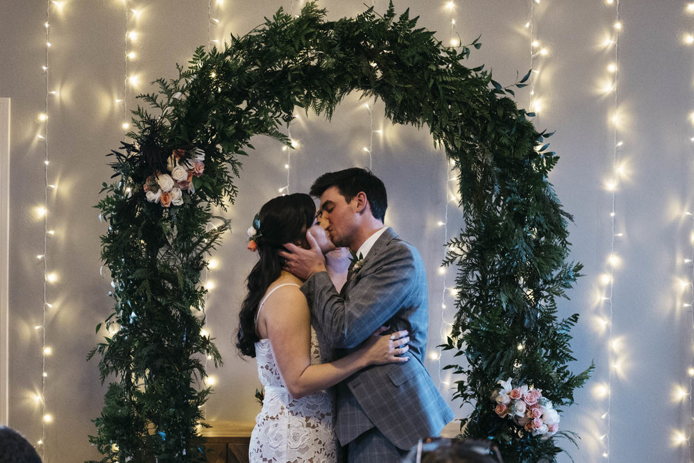 Bride and groom kiss during at-home DIY ceremony.