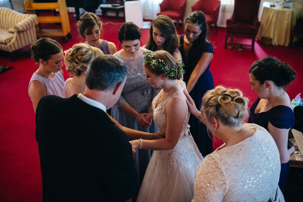 Bride prays with her mother and bridesmaids before her wedding ceremony.