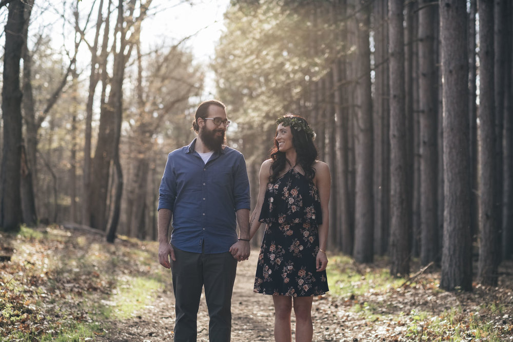 Couple holds hands during their engagement session at Oak Openings Reserve in Ohio.