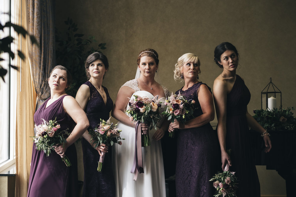 Gorgeous bridesmaids in royal purple with dusty rose bouquets.