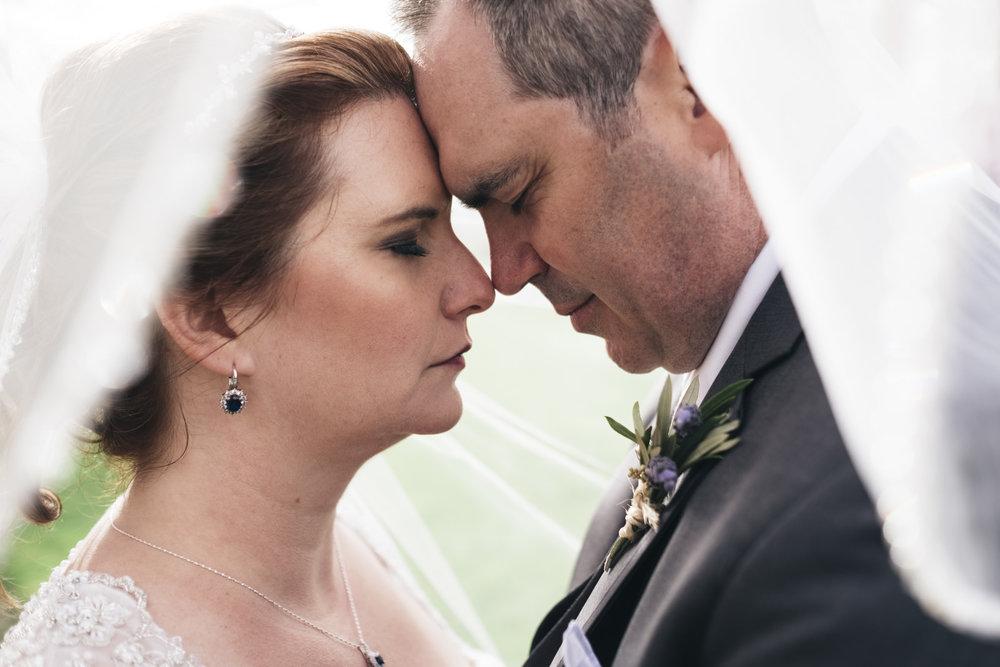 Bride and groom veil portrait