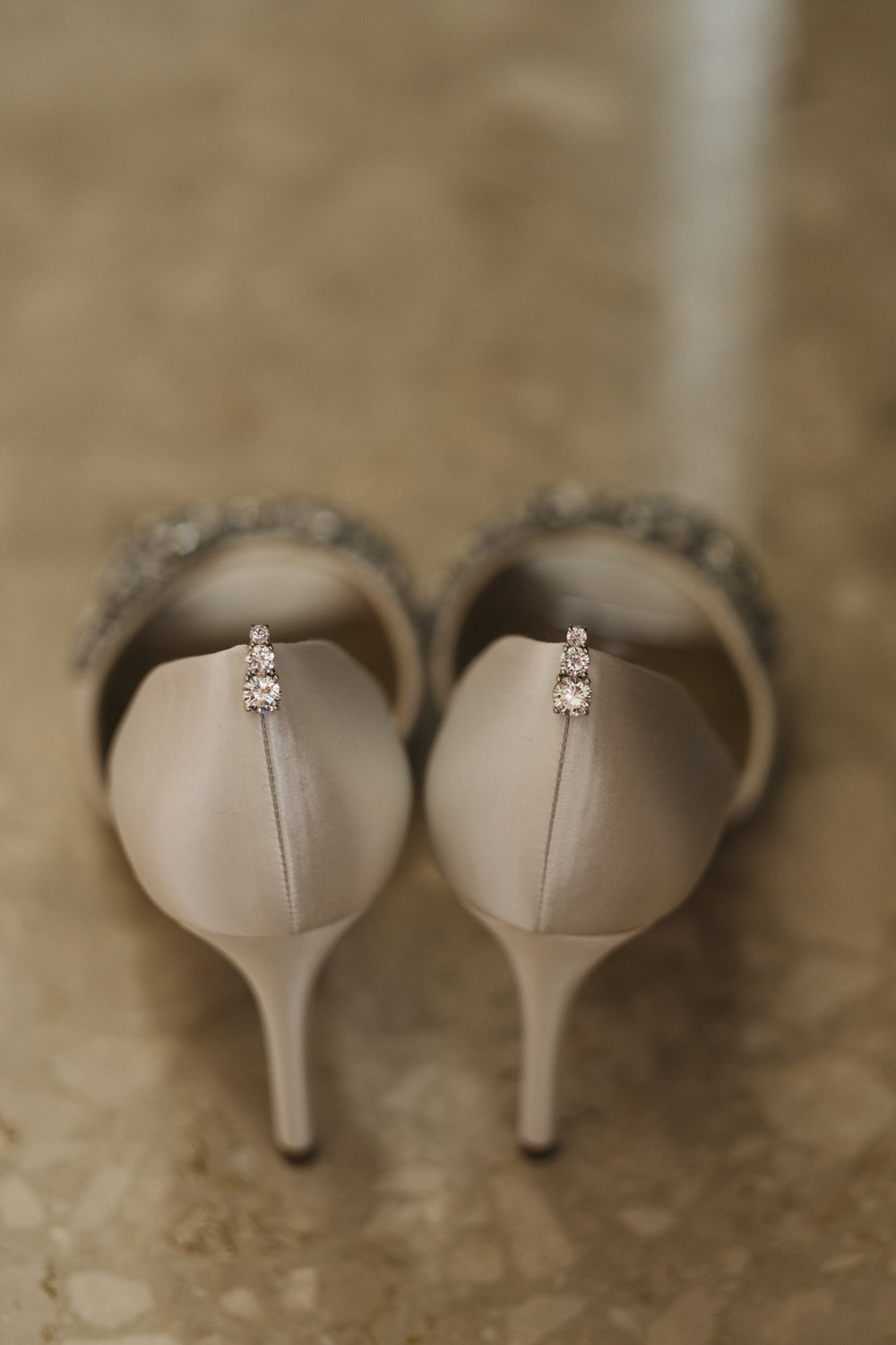 Detail photography of wedding shoes and diamond earrings.