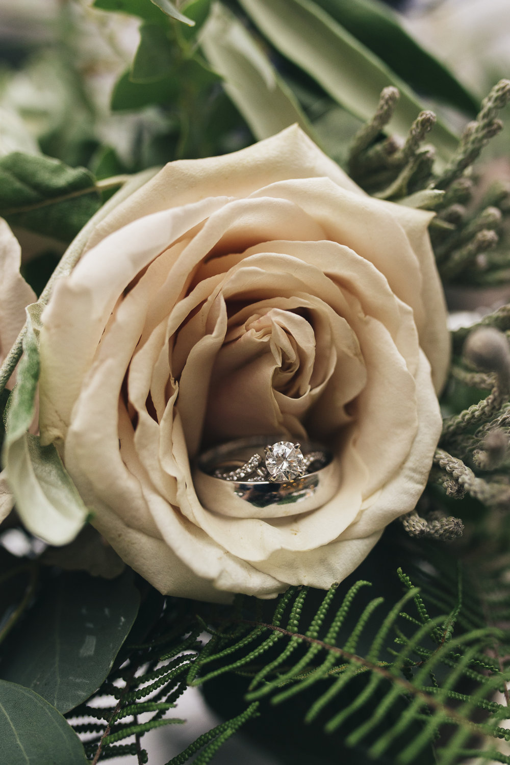 Diamond wedding ring photography in bridal bouquet.