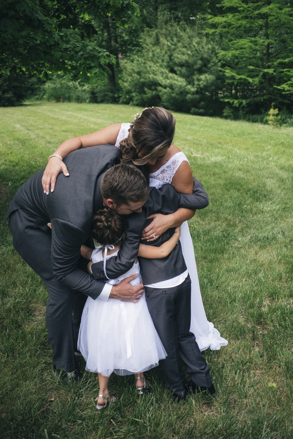 Bride and groom hug children on wedding day in Whitehouse, Ohio.