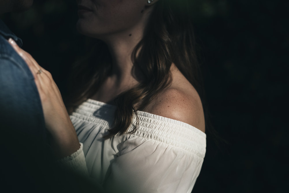 Gorgeous photo of bride-to-be in off-shoulder shirt during engagement session.