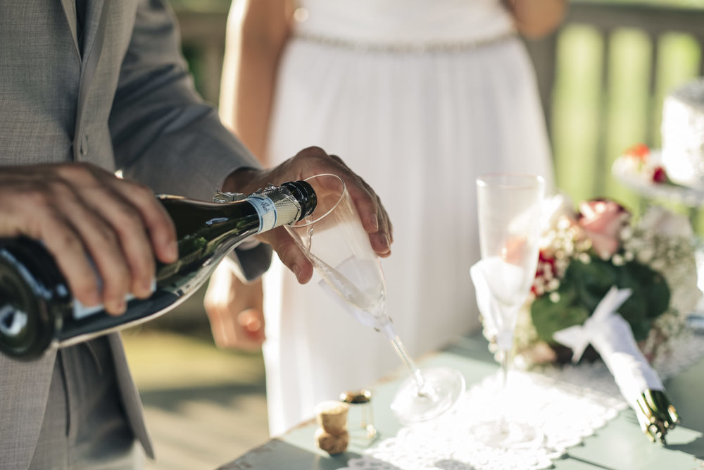 Groom pours a glass of wine following his elopement.
