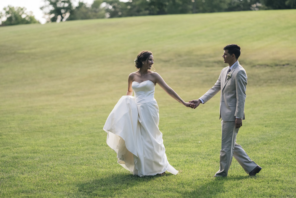 Bride and groom walk across Nazareth Hall grounds in Grand Rapids, Ohio.