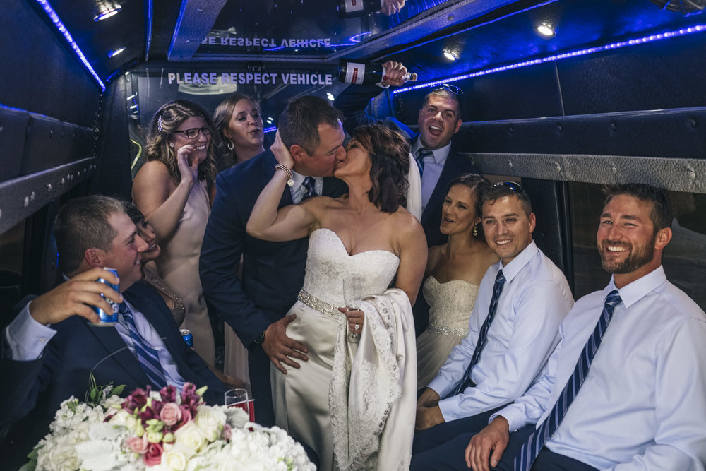 Bride and groom kiss in a Limo Toledo party bus.