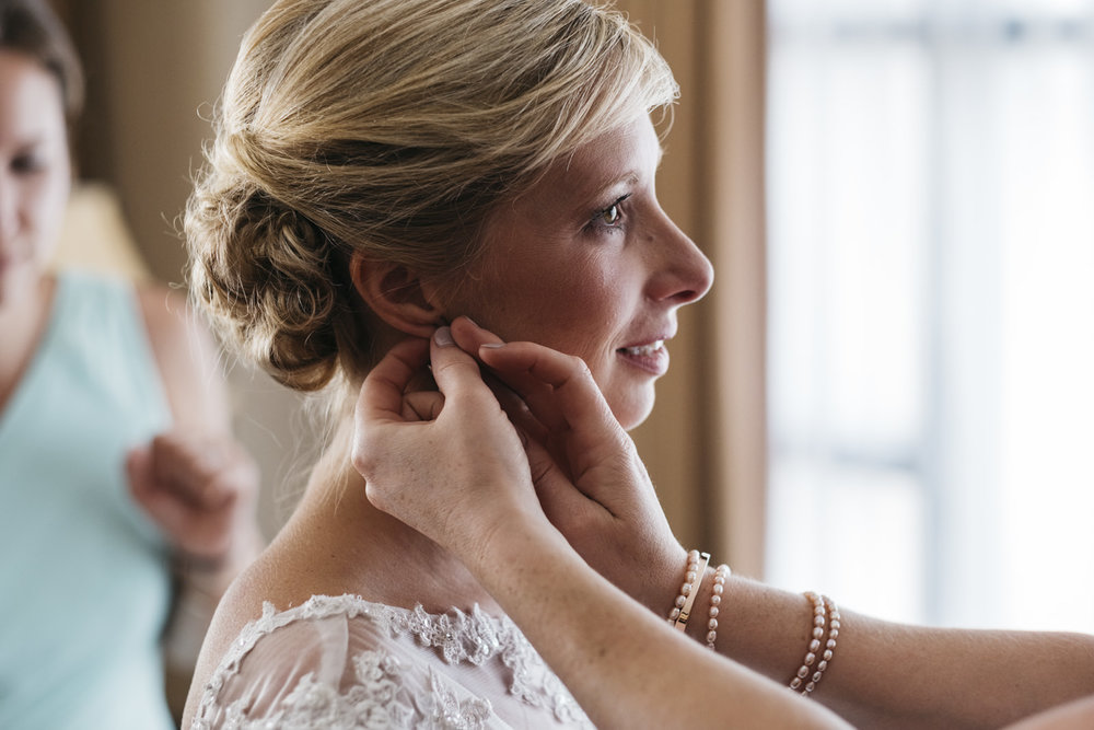 Bride putting earrings on on wedding day.