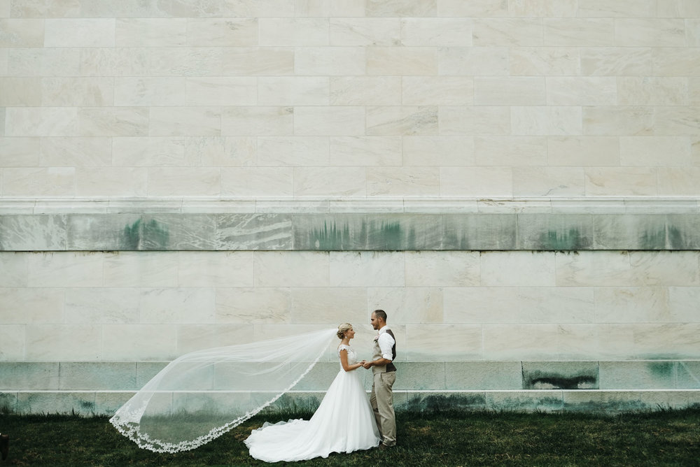 A bride and groom stand in front of a wall in northwest Ohio.