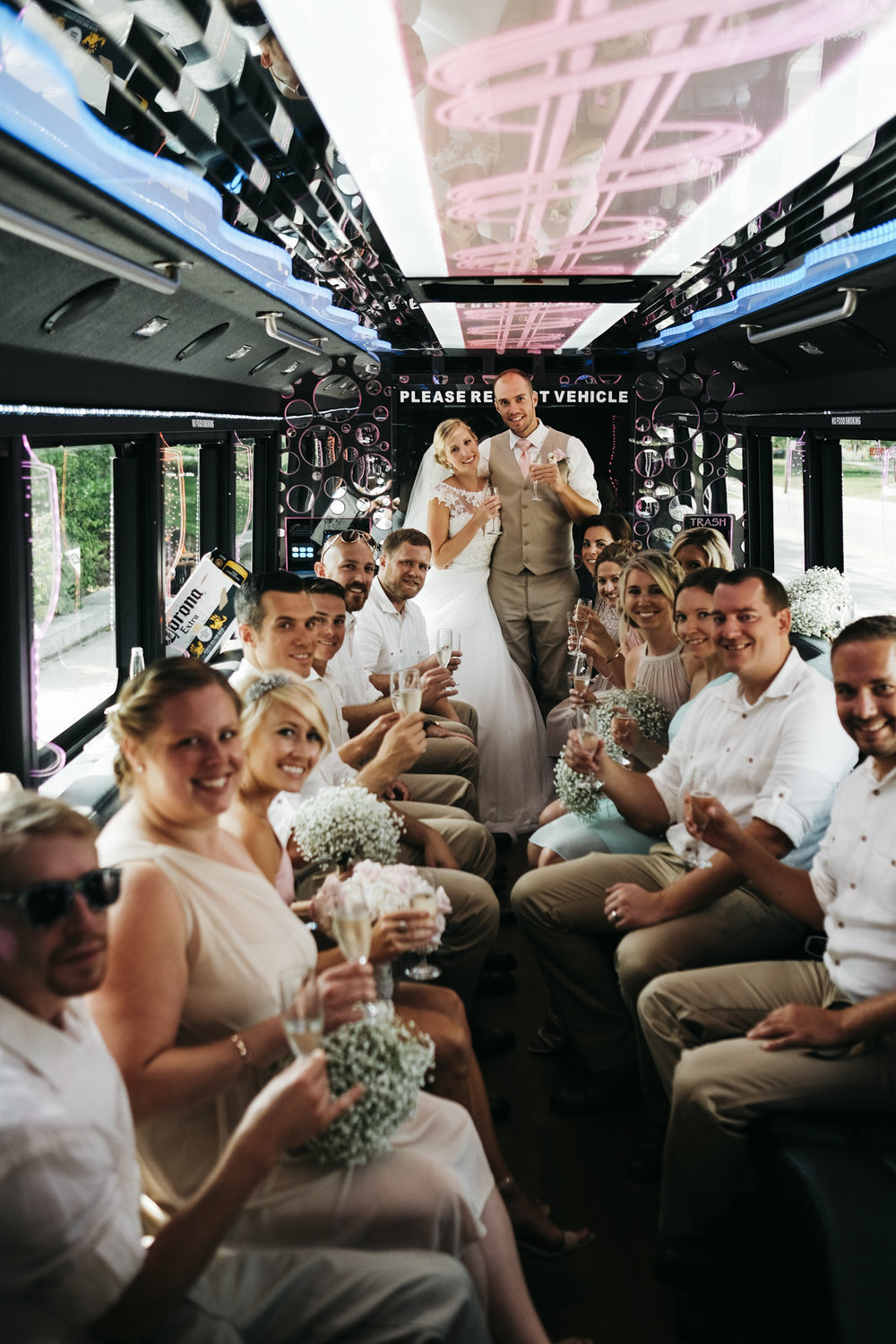 The bride and groom and bridal party of the party bus on the way to the ceremony.