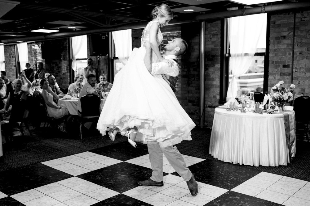 Groom lifts the bride during their wedding reception first dance.