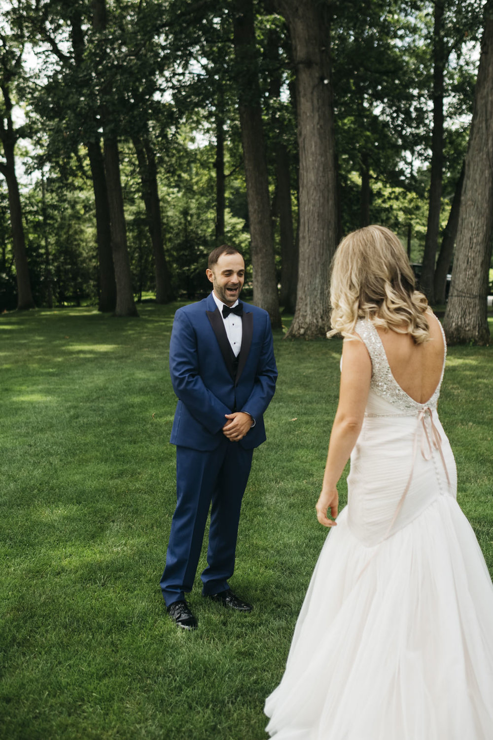 A surprised groom sees his bride for the first time before their wedding ceremony.