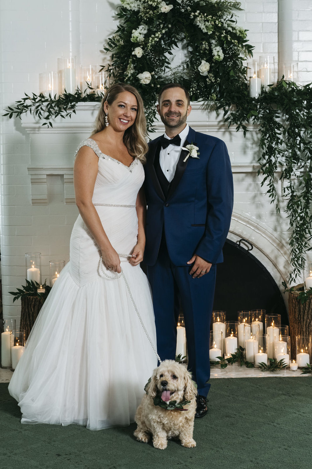 Bride and groom with their dog pose for a picture after their wedding ceremony.