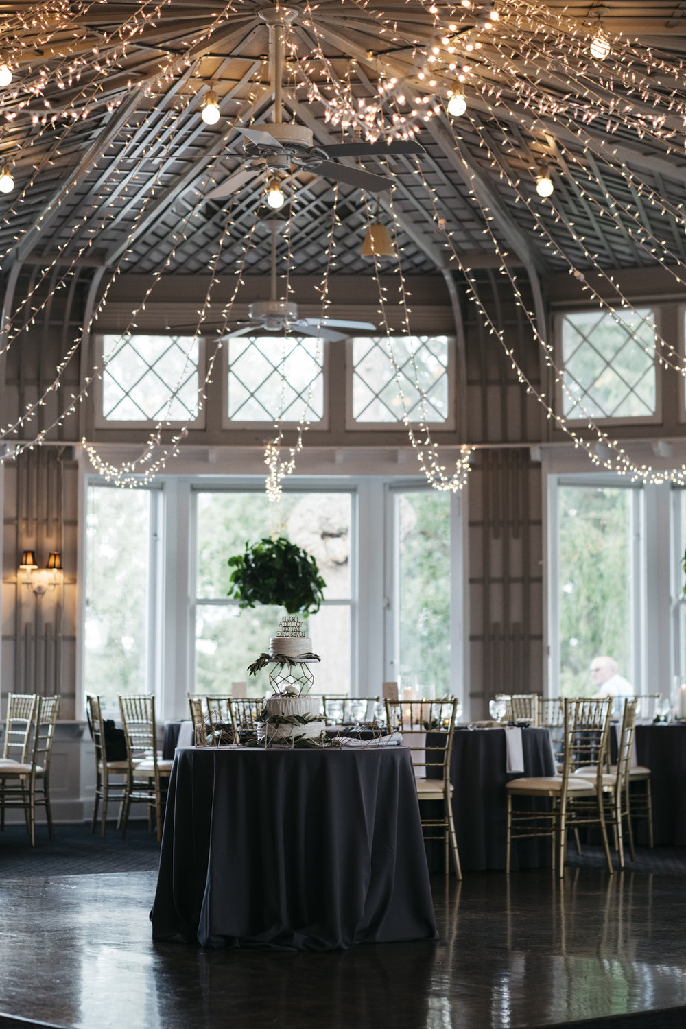 Wedding reception at Toledo Country Club with beautiful string lights and gold details.