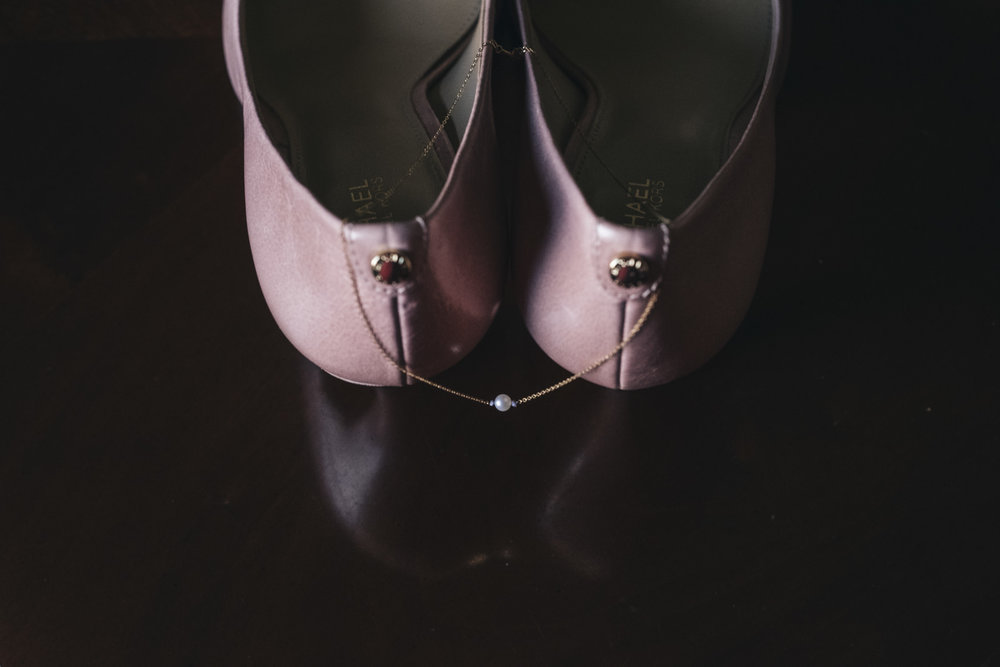 Pink wedding shoes and pearl necklace detail photography.